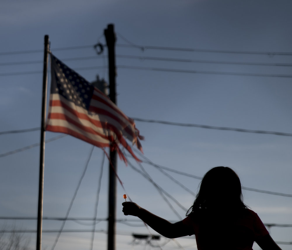 Third grader Lauren Shumway holds up a lollipop while jumping on her trampoline outside of her Nelsonville, Ohio home.