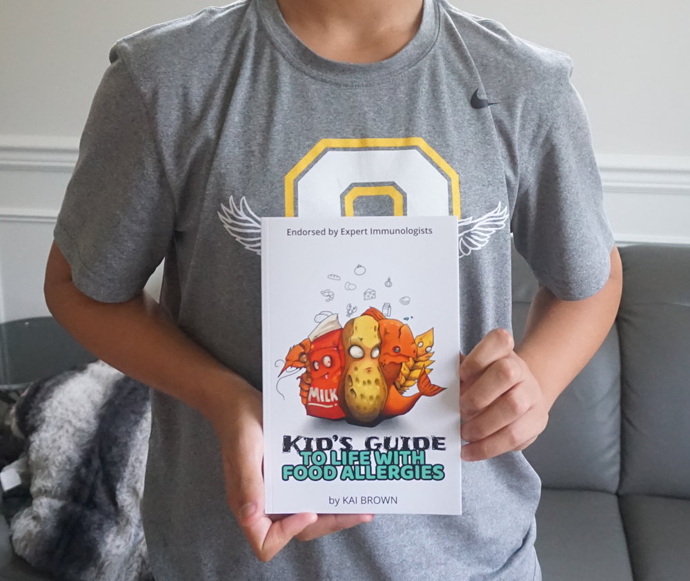 Author Kai Brown with his book  Kid's Guide to Life with Food Allergies