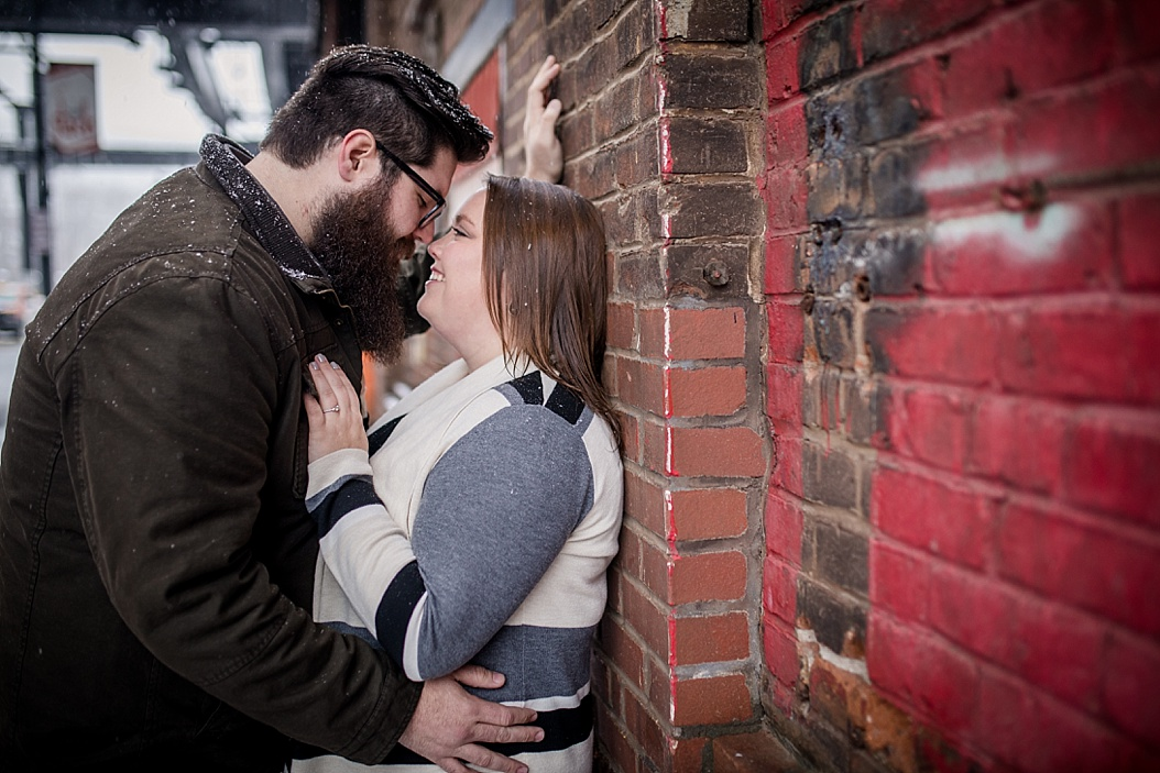 couple kissing against a wall