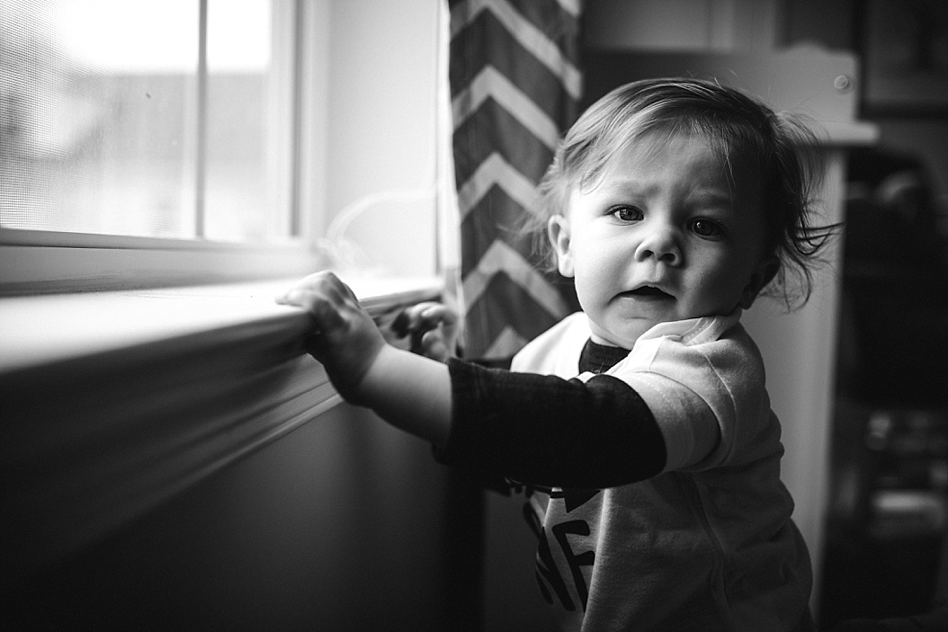 baby standing at window sill