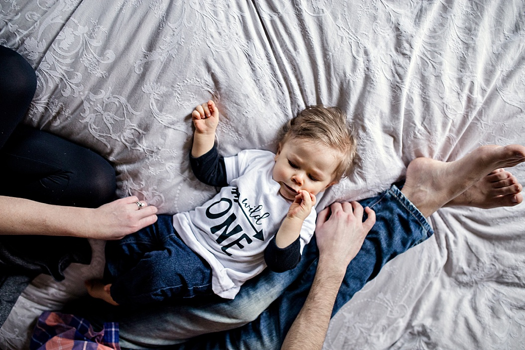 baby laying on bed with parents