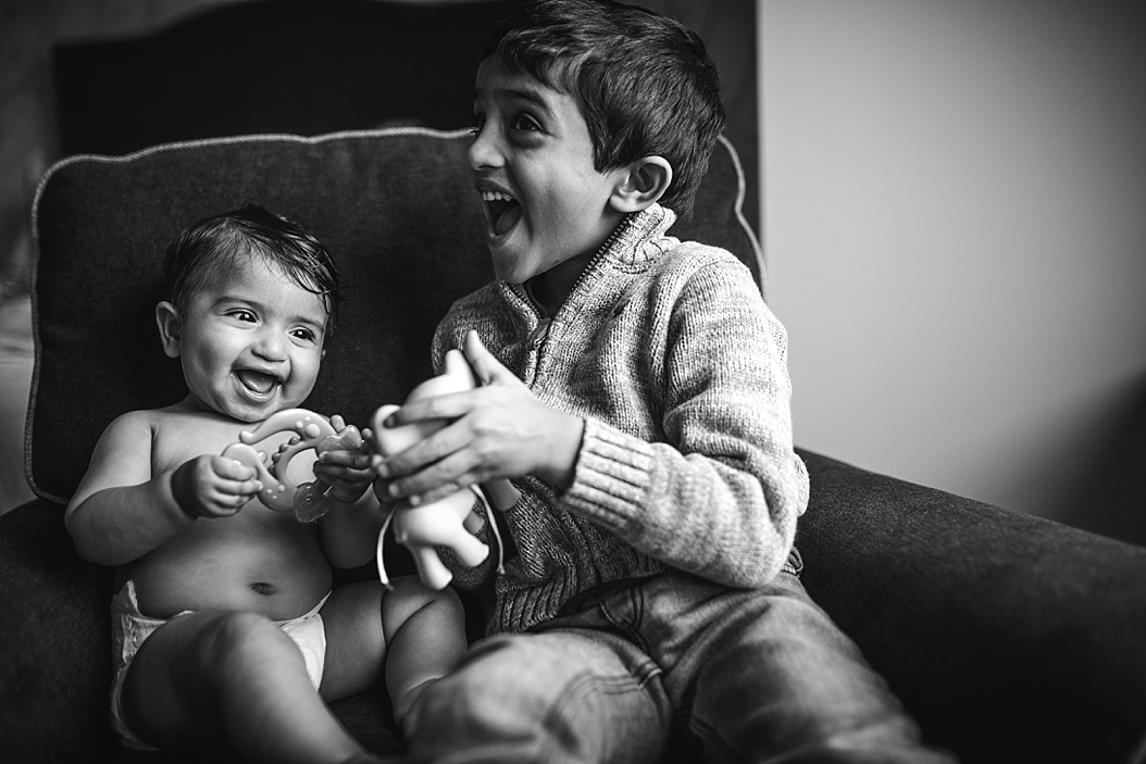 brother and sister laughing in a chair