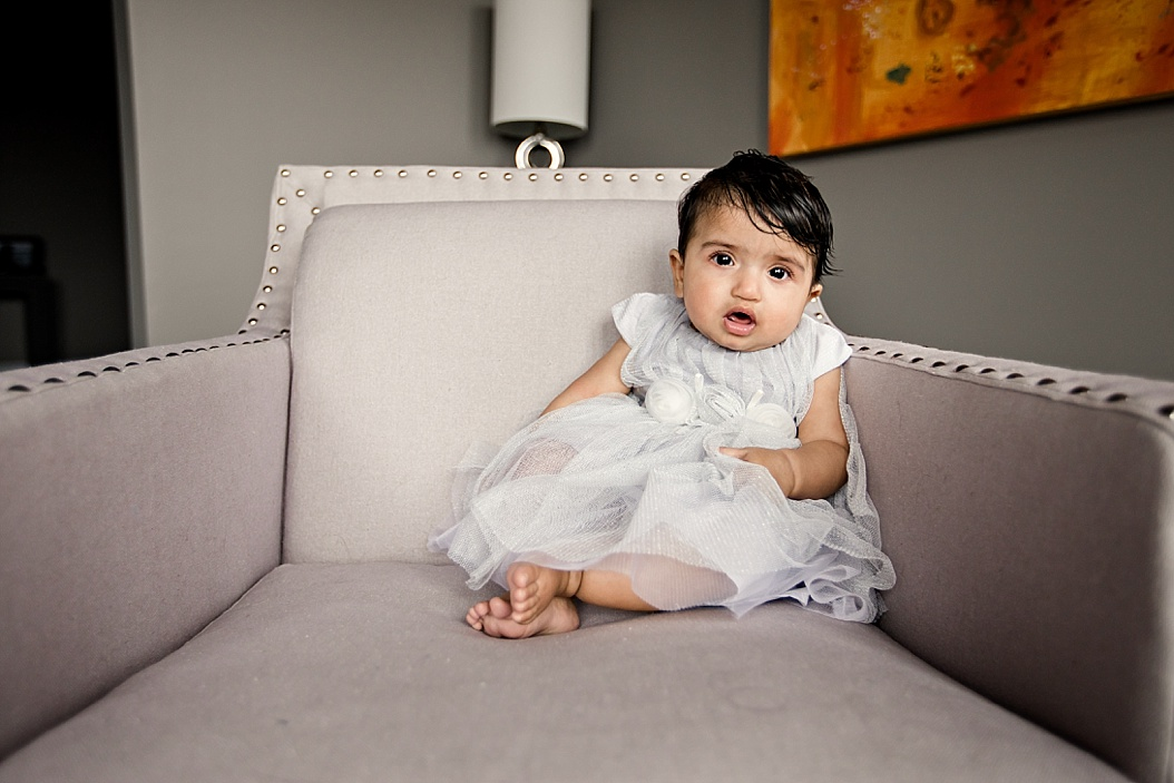 baby girl sitting in a chair with white dress on