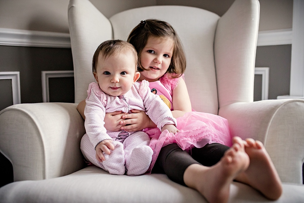 big siste holding little sister in chair