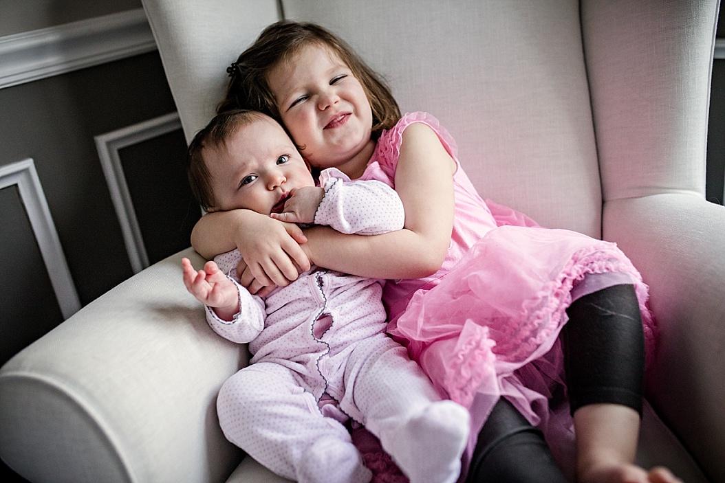big sister hugging little sister around neck