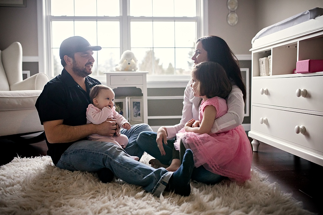 family sitting on white rug in nursery