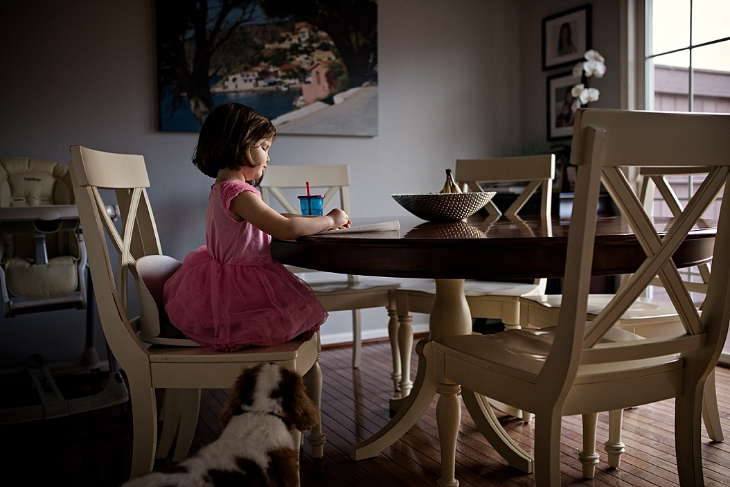 little girl sitting at table eating snack