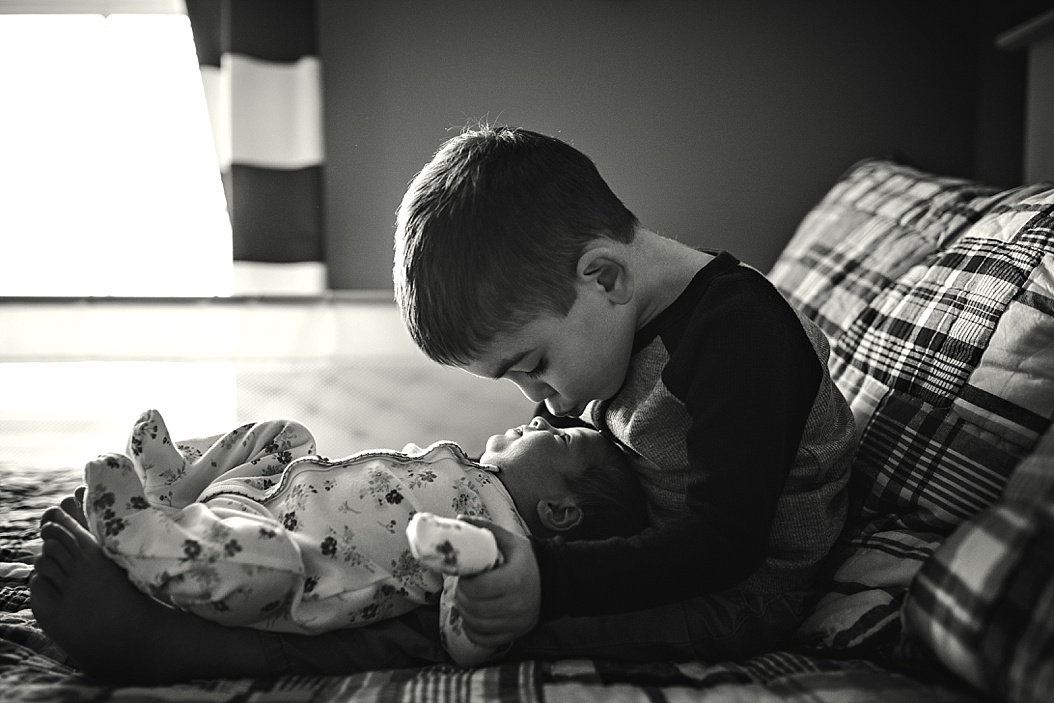 big brother holding little sister in lap kissing her