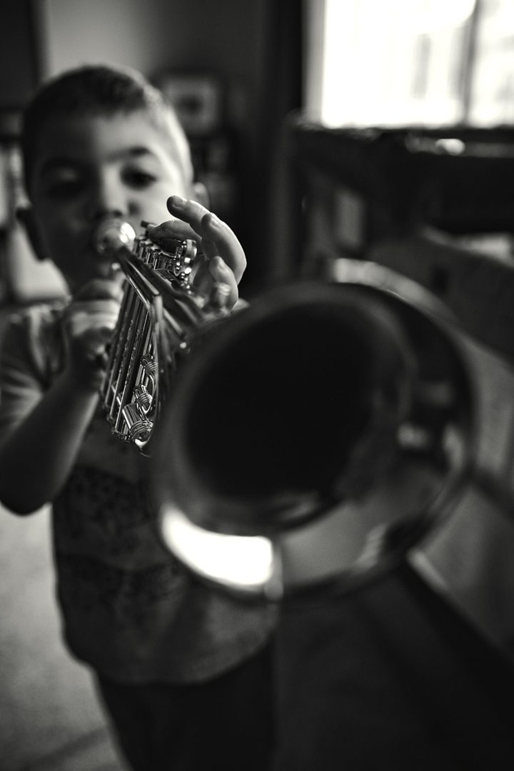 toddler playing trumpet into camera lens