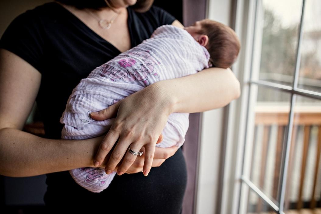 mom holding swaddled baby