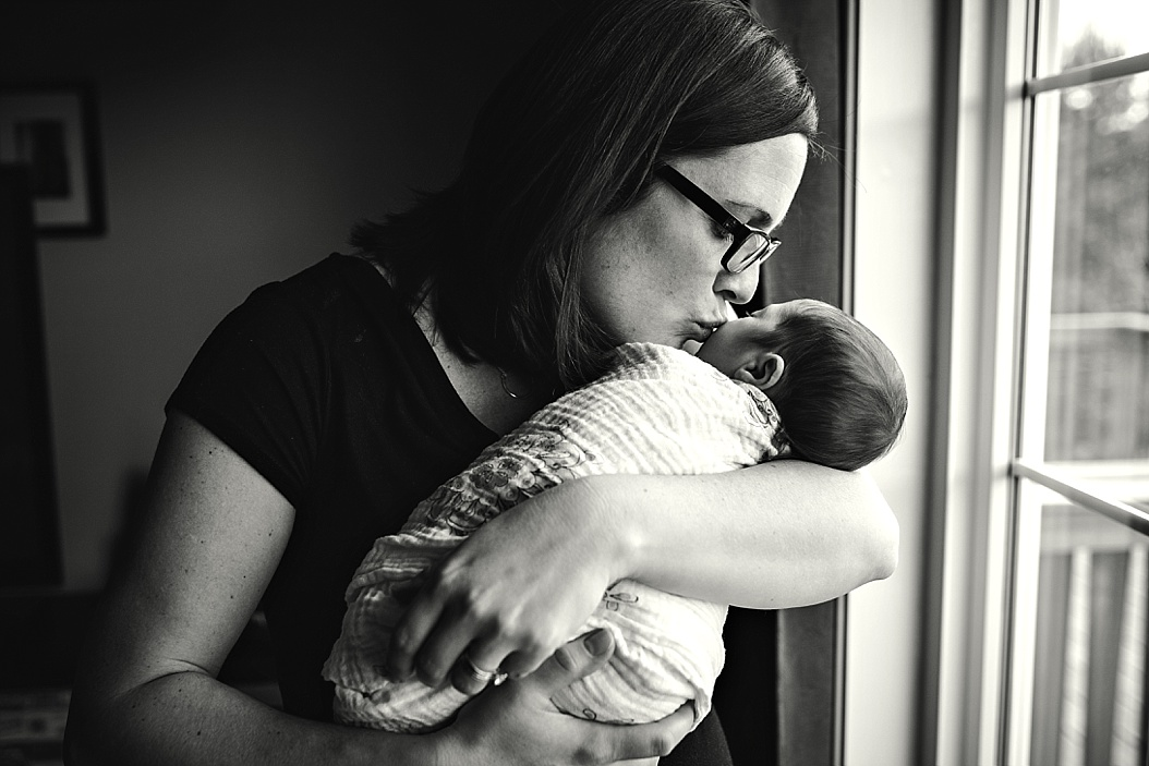 black and white picture of mom kissing baby