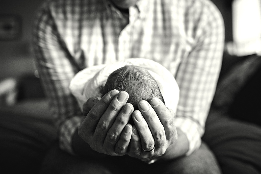 dad holding baby's head and looking down