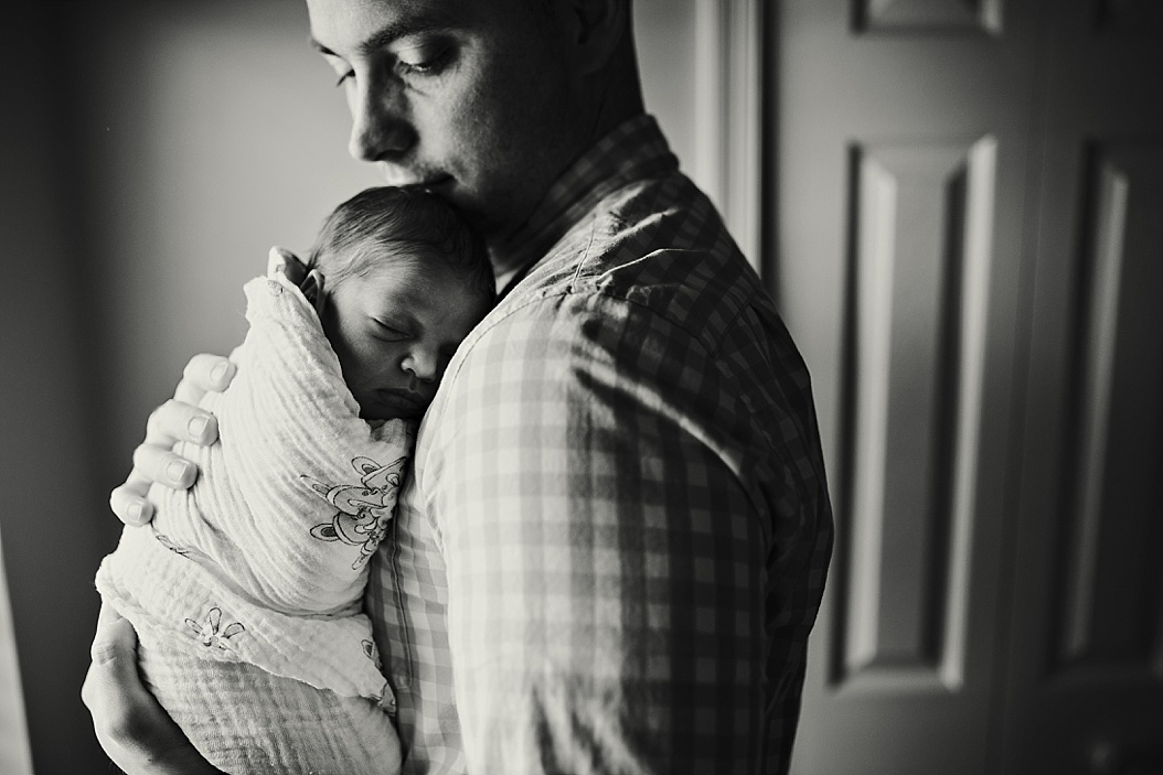 black and white of dad holding baby to chest