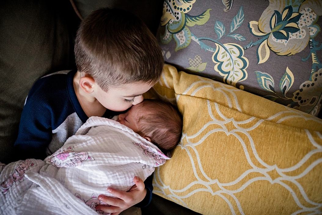big brother kissing little sister on couch