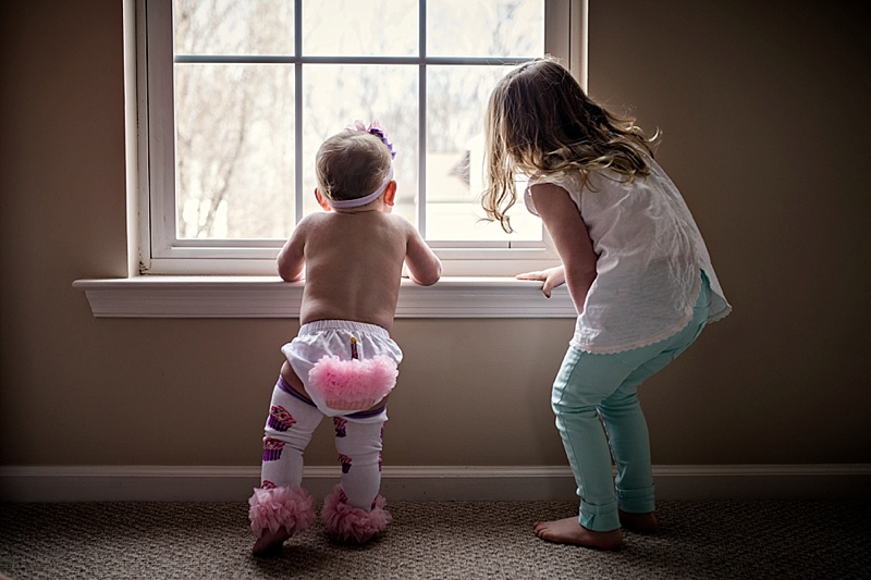 toddler sisters looking out window