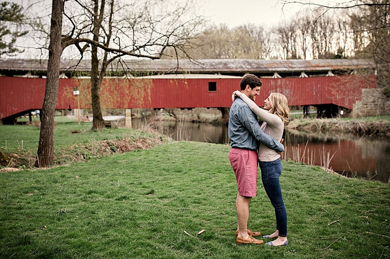 couple standing by red covered bridge