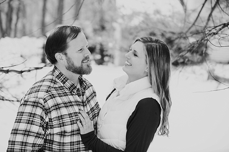 black and white of couple laughing in the snow
