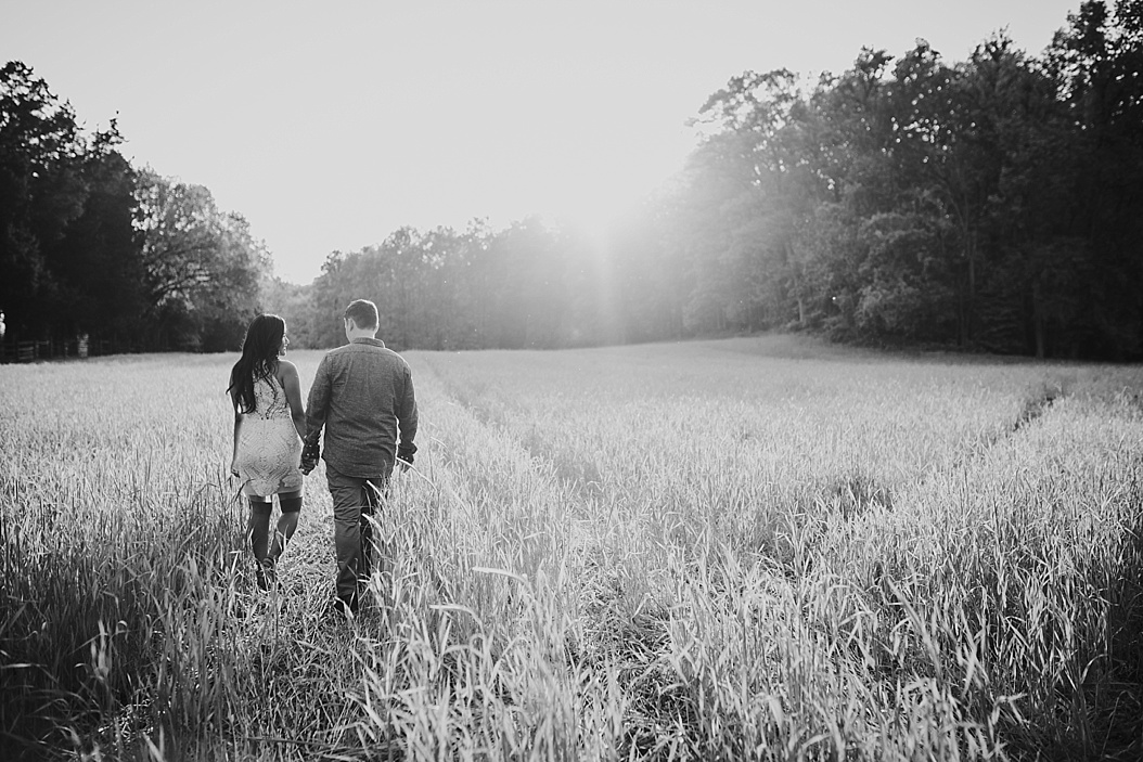 black and white of couple walking in high grass field