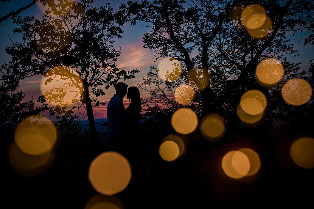 sunset silhouette of couple on top of mountain