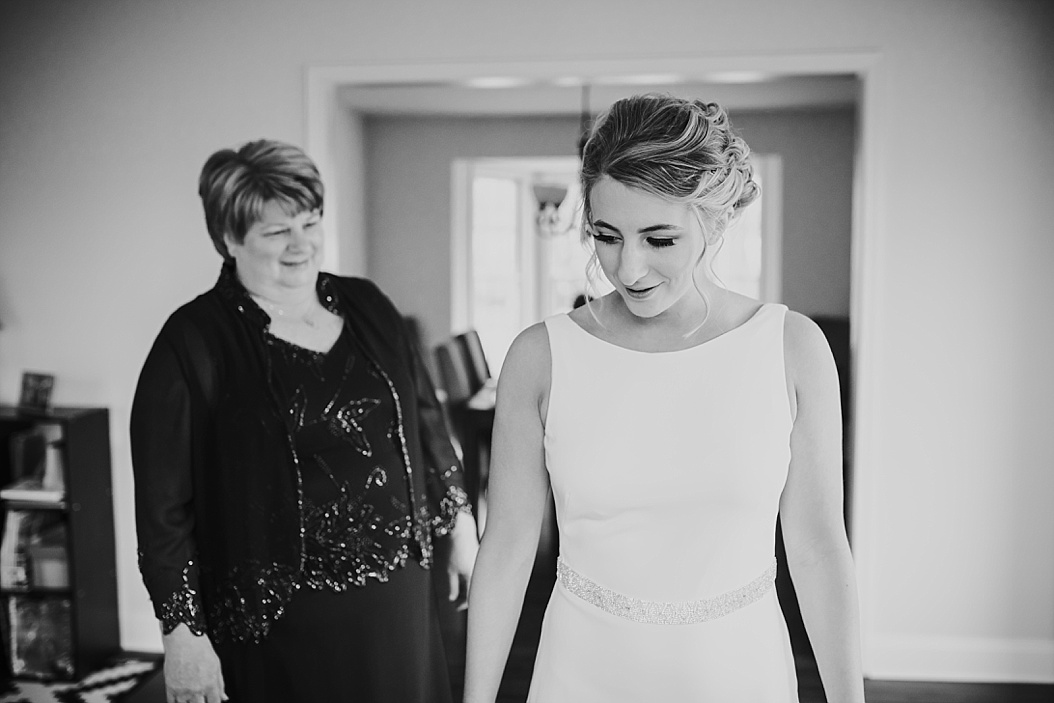 mother of bride admiring bride in wedding dress