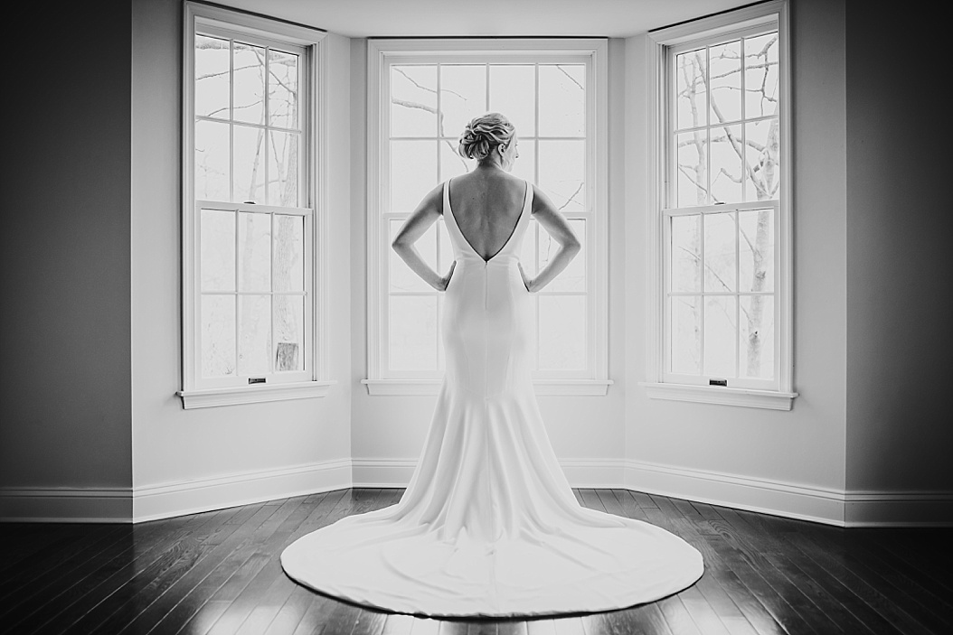 bride standing in bay window in wedding dress