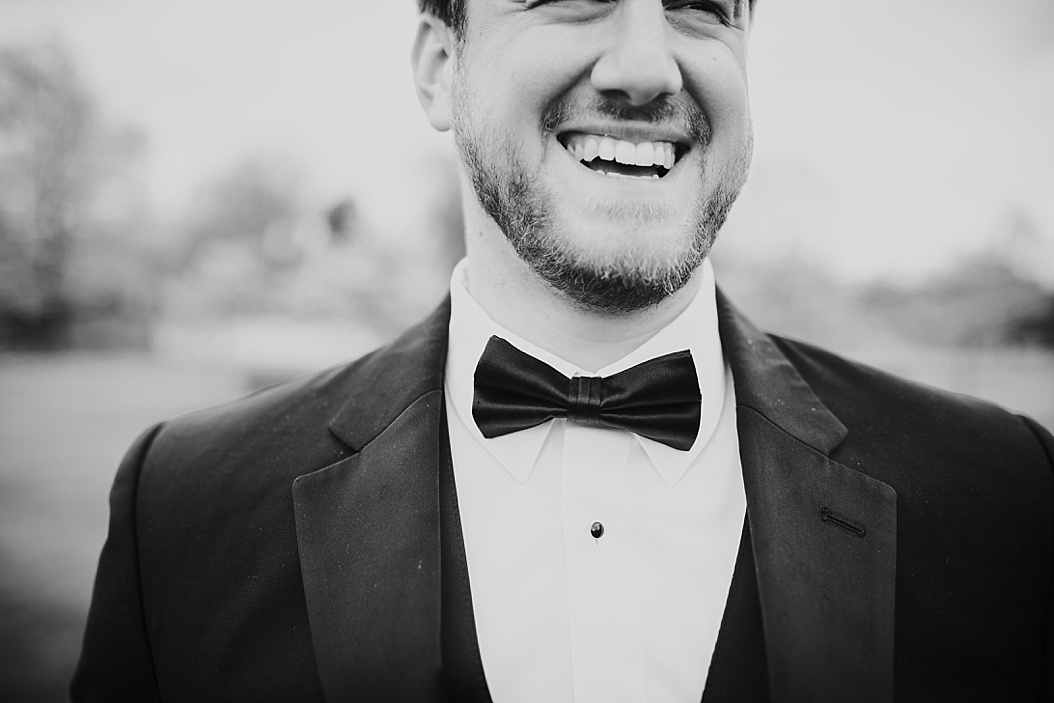 close up shot of groom laughing wearing a bowtie