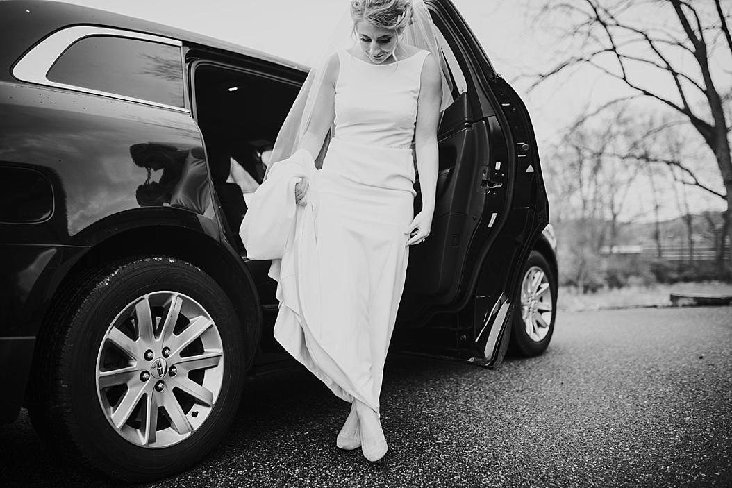black and white of bride stepping out of car