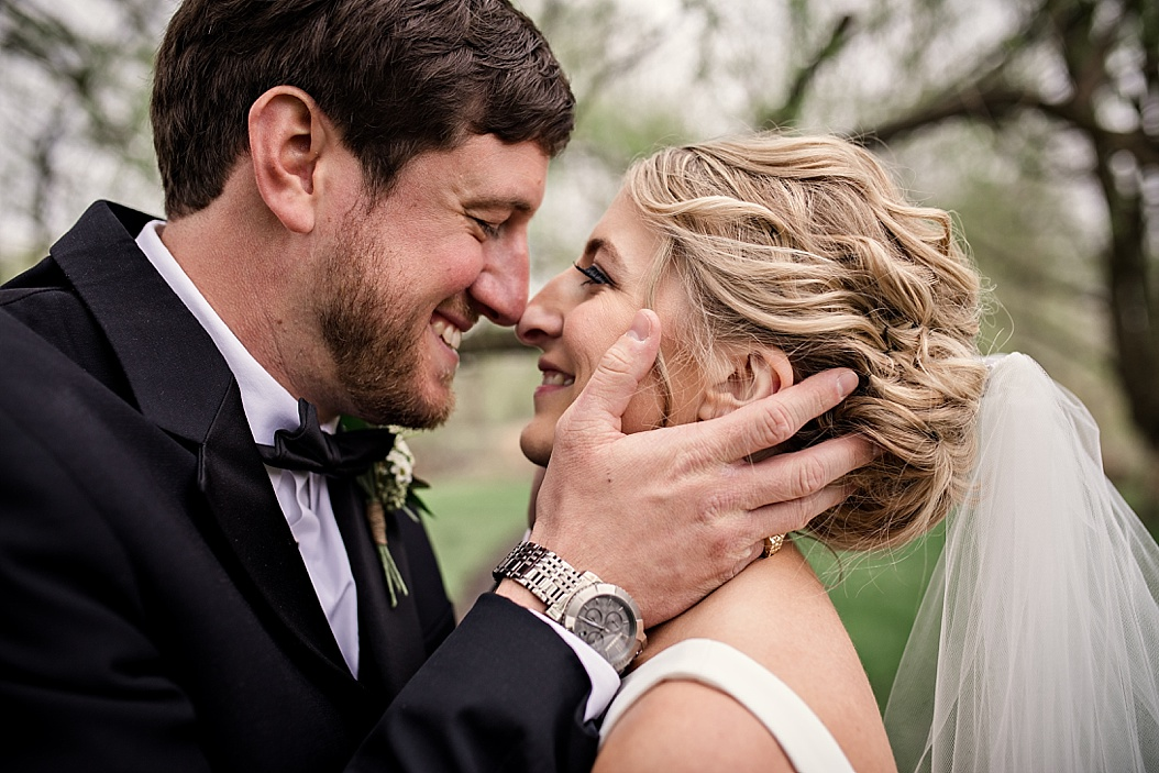 groom holding bride's face sharing laughs