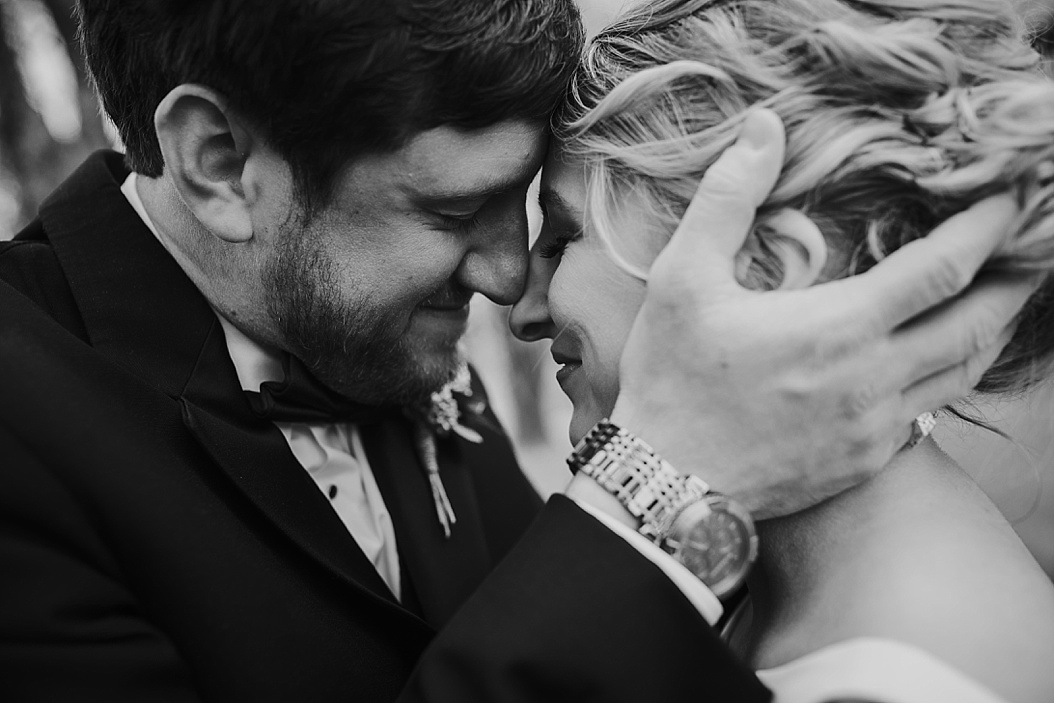 groom holding brides face sharing an intimate kiss