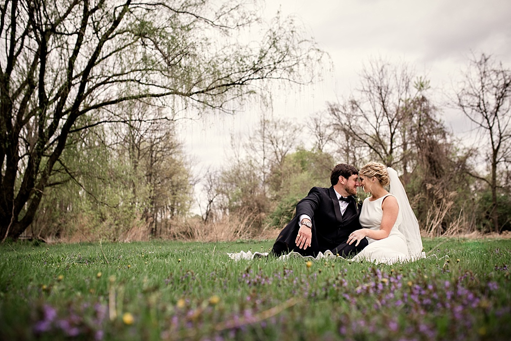 bride and groom sitting in meadow forehead to forehead