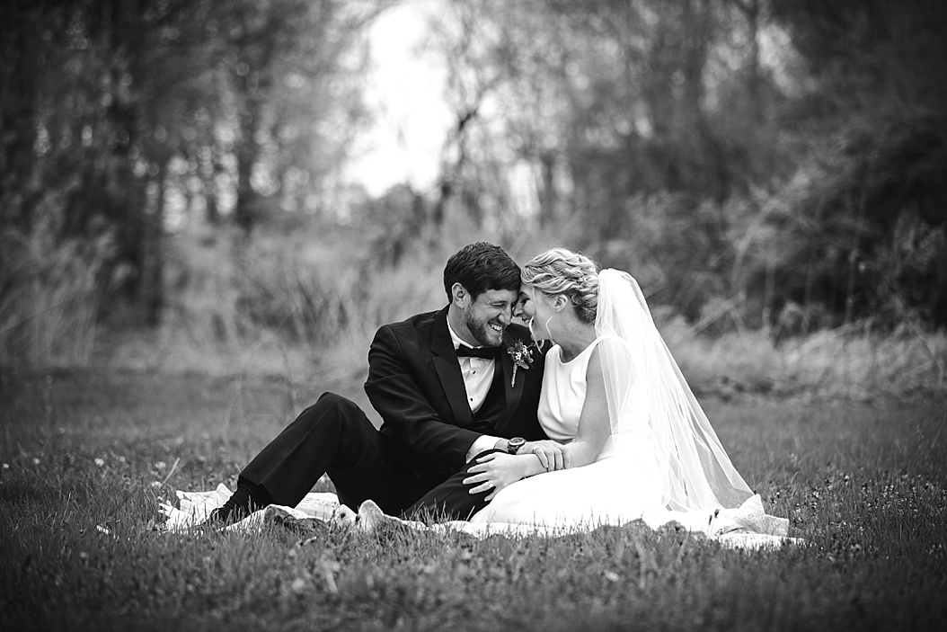 bride and groom laughing in meadow