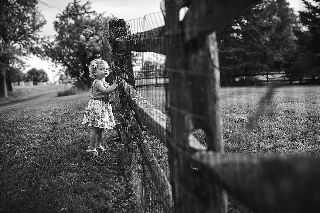 toddler standing at split rail fence