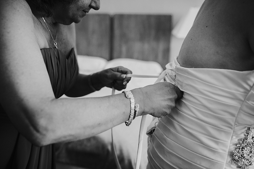 mom lacing back of bride's dress