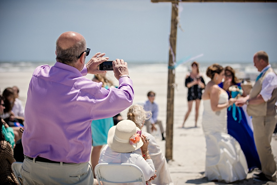 father taking picture of bride saying vows