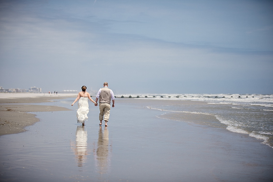 bride and groom making footsteps in the sand