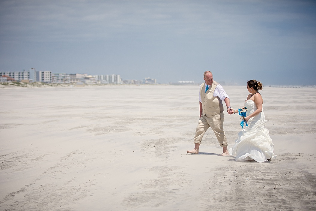 groom leading bride walking on the beach