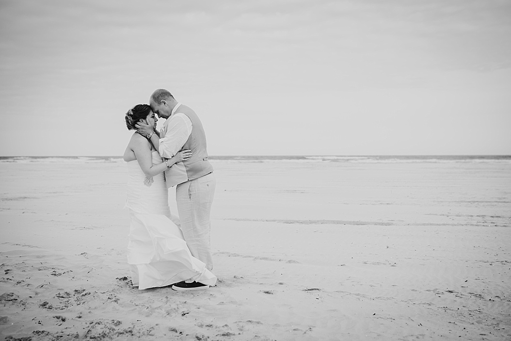 black and white image of groom holding bride's face