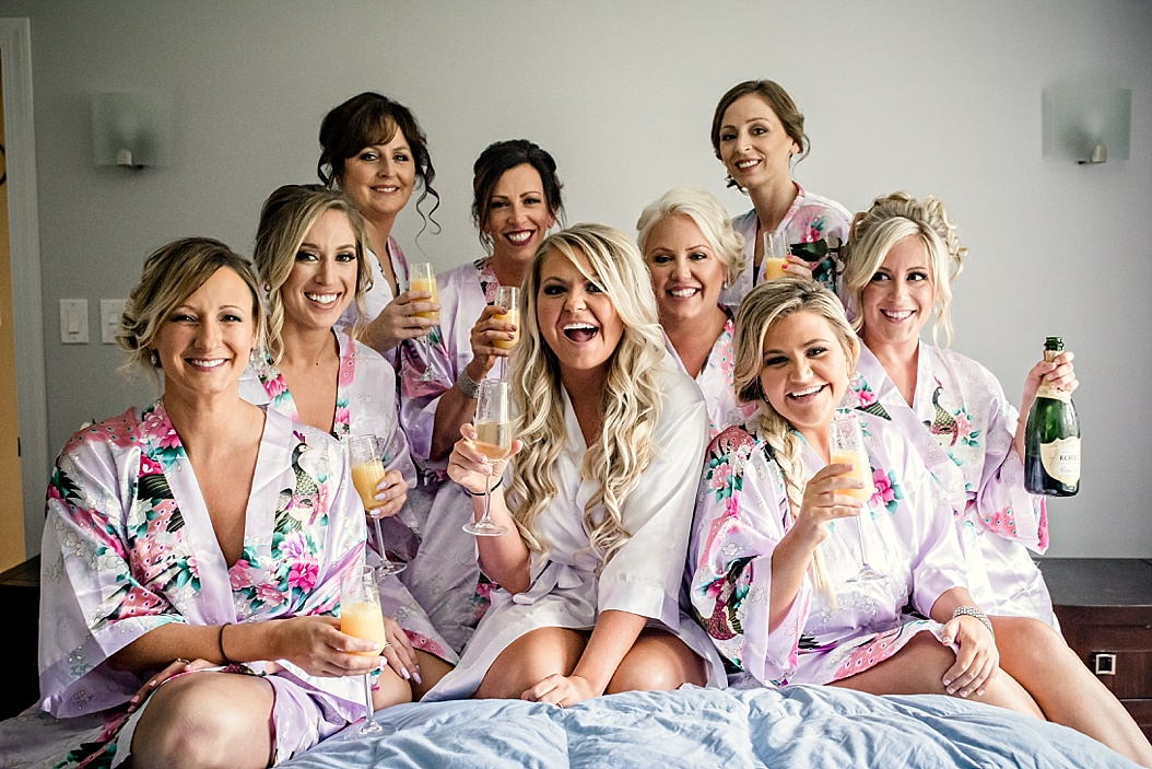 bride sitting on big with bridesmaids