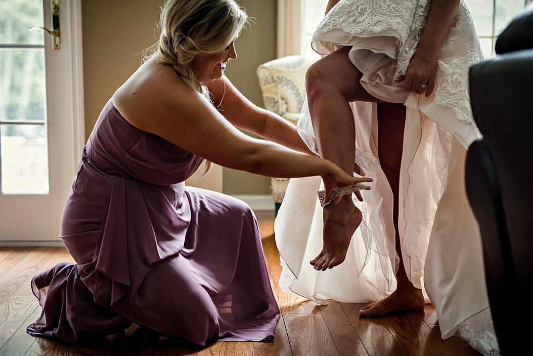 maid of honor putting garter on bride