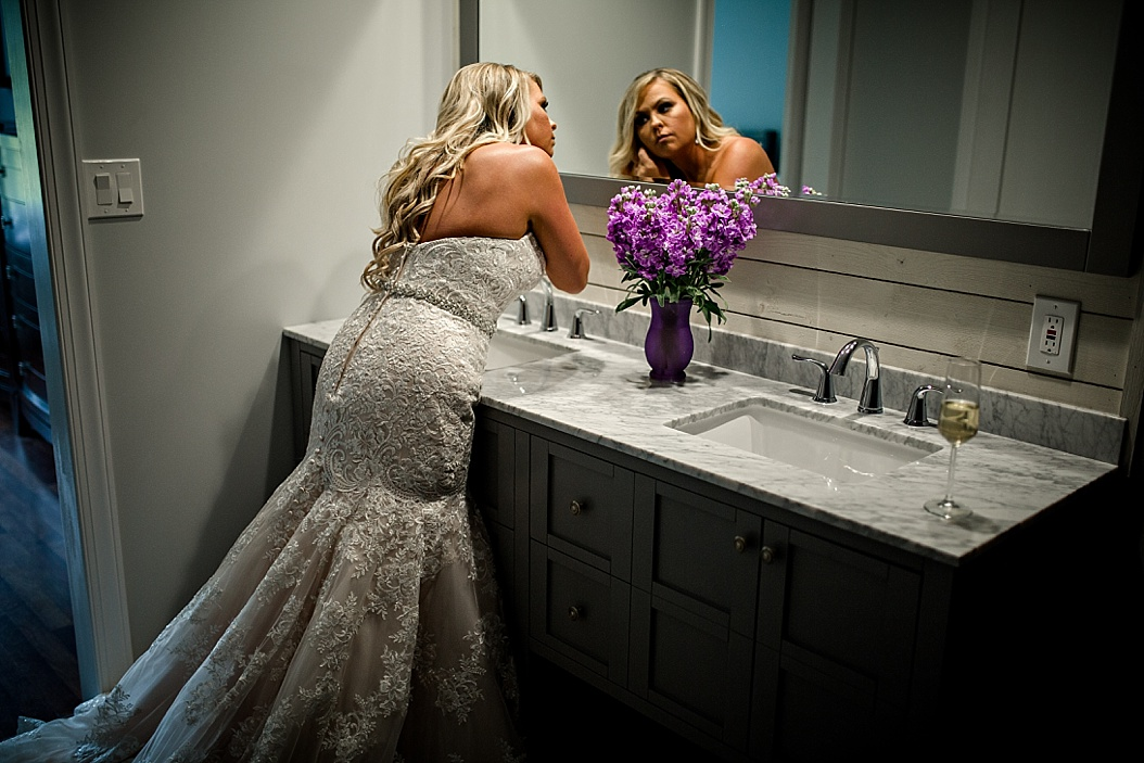 bride using mirror to put on jewelry