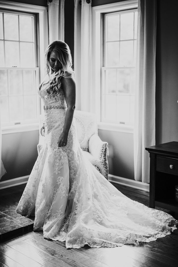 black and white of bride standing alone in wedding gown