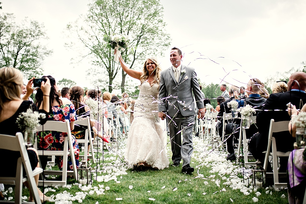 bride and groom recessional with arms in the air