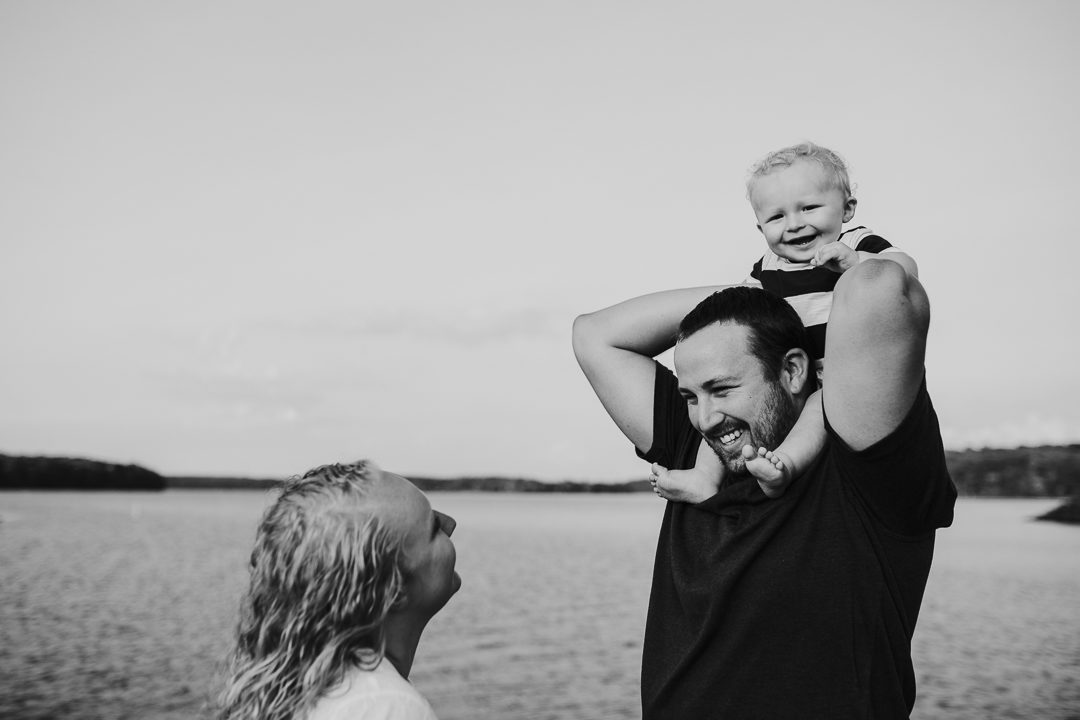 boy on dad's shoulders laughing