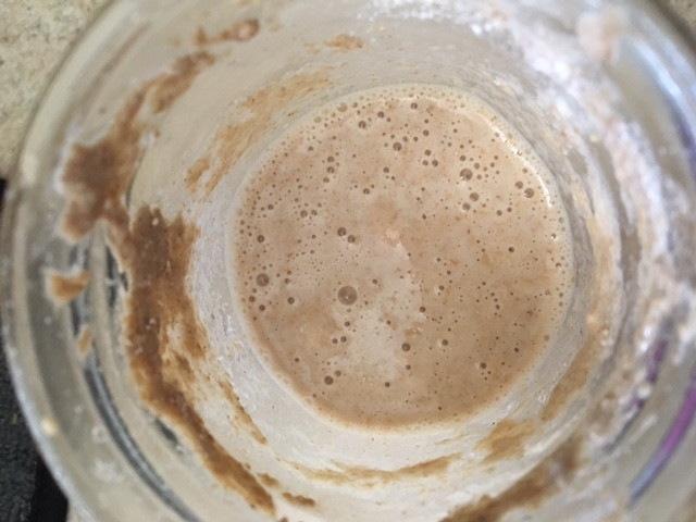 [Image: a jar of bubbling sourdough starter, light brown in color]