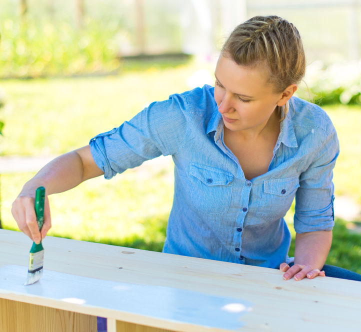 42097365 - woman with brush painting wooden furniture.