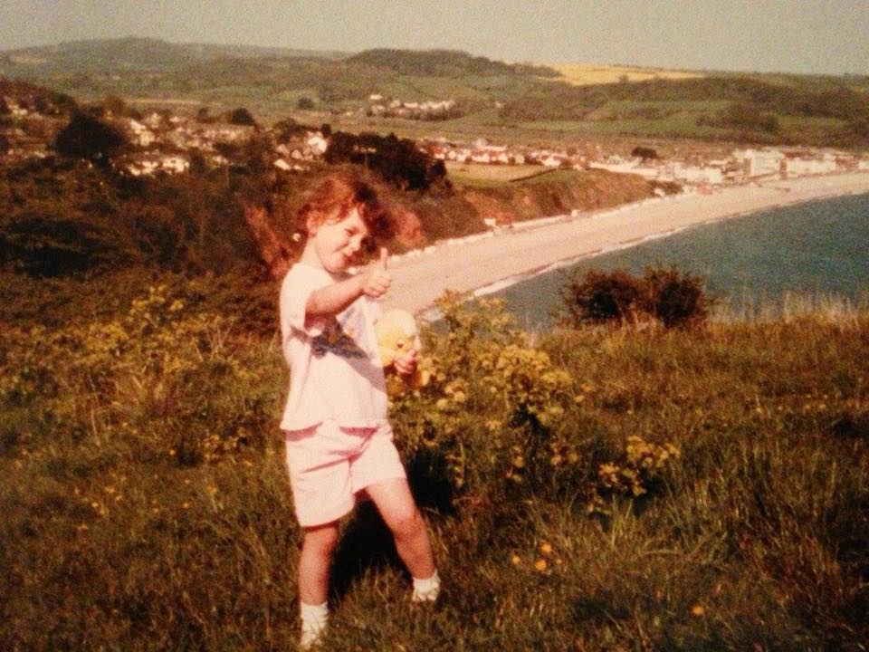 """Charlotte Katherine – """"In the late 80s/early 90s doing a favourite clifftop walk in Devon. I always had to take a cuddly toy on my walks."""""""