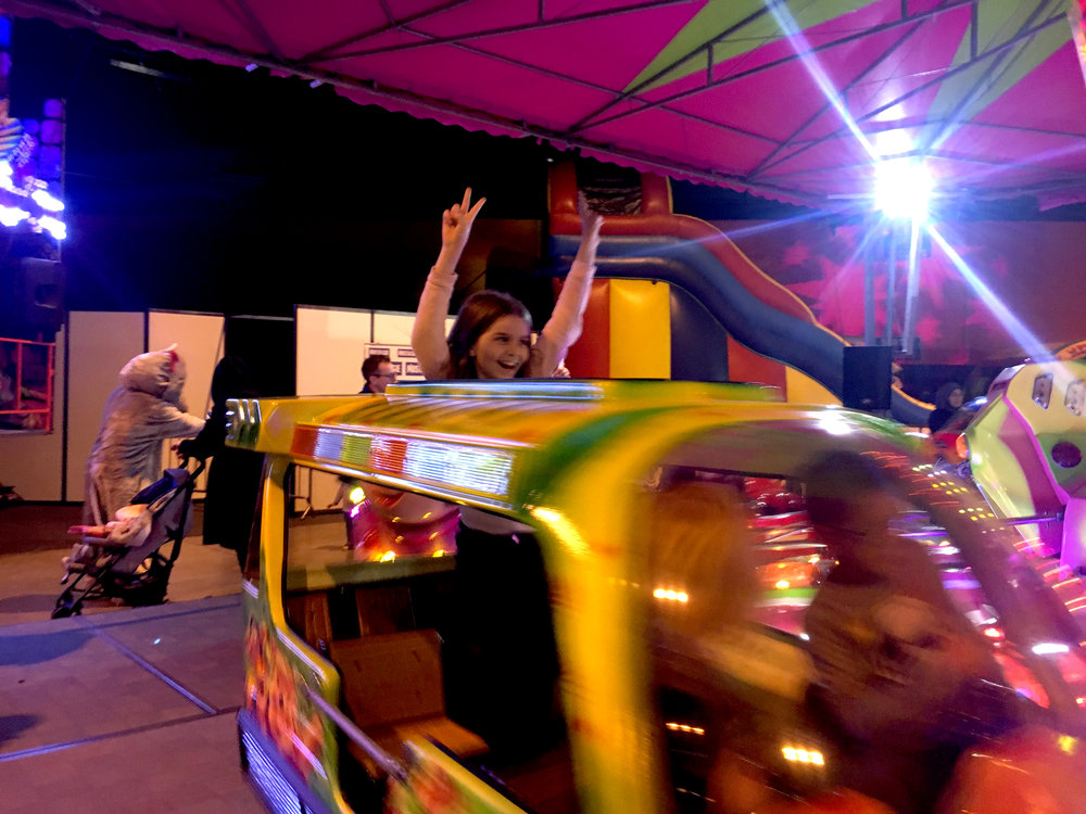 Elma rides one of the many carnival rides at the fun fair. The event had multiple games and rides for the families such as an air rifle game and bumper cars. Photo courtesy:  Amy Nakamura .