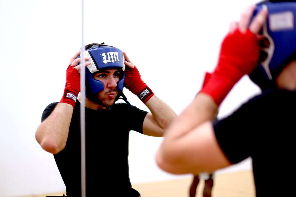 Georgios Michopoulos adjusts his protective gear during a Monday practice in Flanagan Gym. Photo by Jiaman (Maggie) Peng.