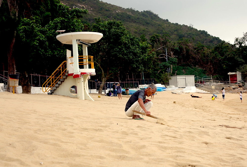 A man spends hours sweeping this beach on Llama Island, Hong Kong. Photo courtesy:  Kuba Wasowicz .