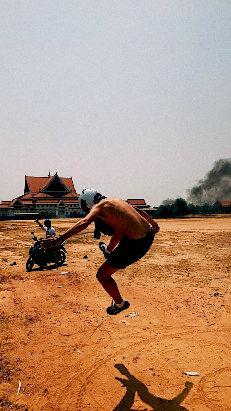 Burning tires in the middle of a field, right before partaking in a motorbike expedition across Cambodian villages. Photo courtesy:  Kuba Wasowicz .